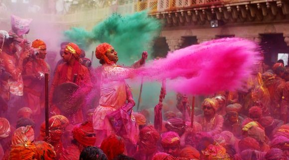 "People throw coloured powder as they celebrate ""Lathmar Holi"" at Nandgaon village in the northern Indian state of Uttar Pradesh, March 22, 2013. In a Holi tradition unique to Nandgaon and Barsana villages, men sing provocative songs to gain the attention of women, who then ""beat"" them with bamboo sticks called ""lathis"". Holi, also known as the Festival of Colours, heralds the beginning of spring and is celebrated all over India. REUTERS/Ahmad Masood (INDIA - Tags: RELIGION SOCIETY) - RTR3FC9U"